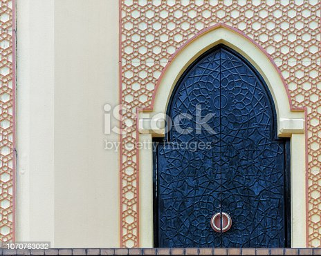 istock Traditional arabesque pattern on the wall, arched iron door with decorative ornament 1070763032