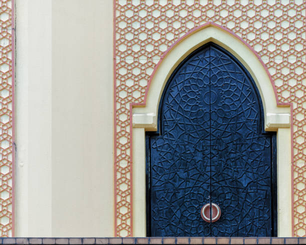 traditional arabesque pattern on the wall, arched iron door with decorative ornament - arabesco stili foto e immagini stock