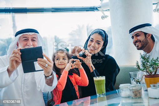 469930796 istock photo Traditional Arabian family taking selfie at cafe 476208748