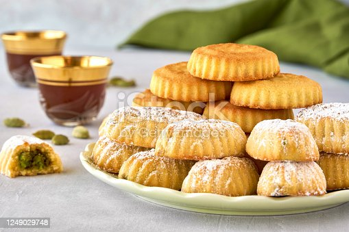 963384046 istock photo Traditional arabic eid sweets. Maamoul or mamoul cookies with pistachios and walnut . Close up 1249029748
