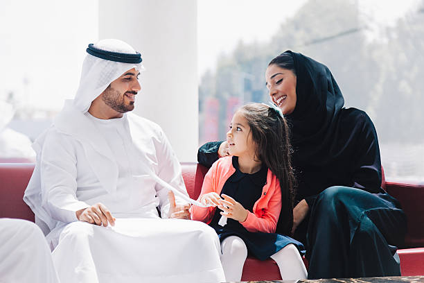 Traditional  Arabic family enjoying at lounge Traditional 3 generation middle eastern family wearing traditional arabic clothes (mother, father, grandfather and daughter) sitting, talking and having fun at lounge of shopping mall at sunny weekend day. Dubai, United Arab Emirates, UAE. arabia stock pictures, royalty-free photos & images