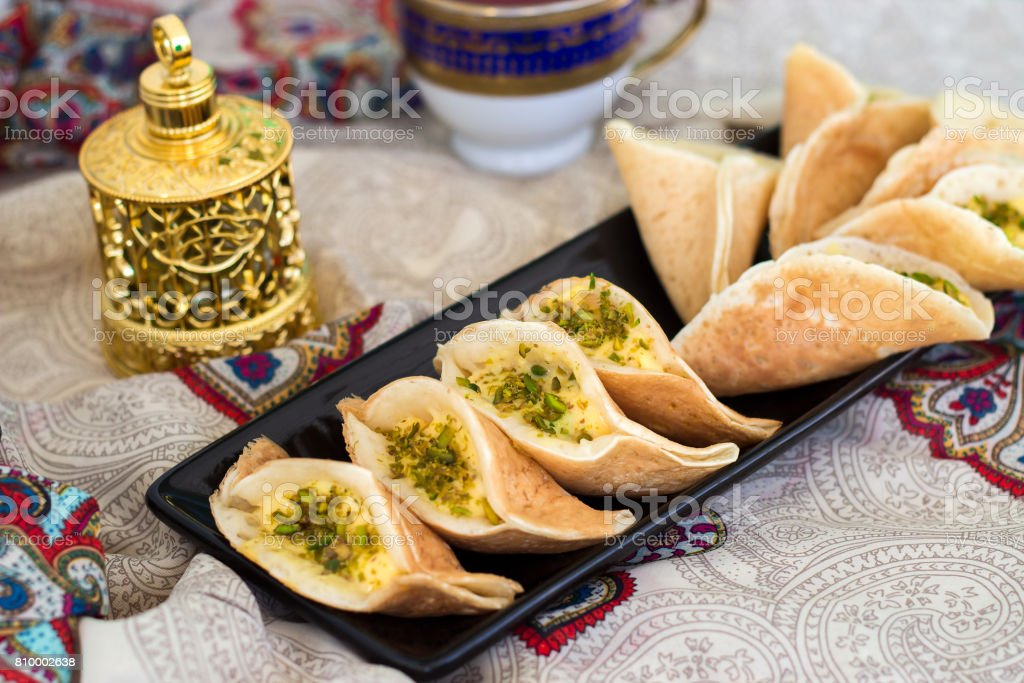 Traditional Arabic kataif crepes stuffed with cream and pistachios, prepared for iftar in Ramadan, oud in gold, on paisley background stock photo