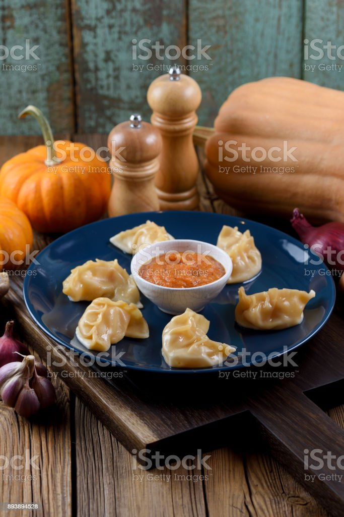 Traditional Asian dish. Crescent shape imperfect dumplings with spicy sauce served with garlic, onion and pumpkin on oak board stock photo