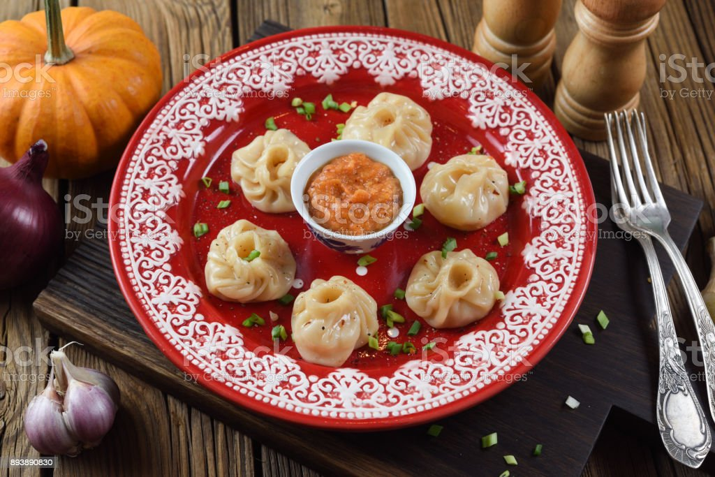 Traditional Asian food. Nepalese dumplings momo with curry sauce served with leek, onion, garlic and pumpkin on bright red plate stock photo