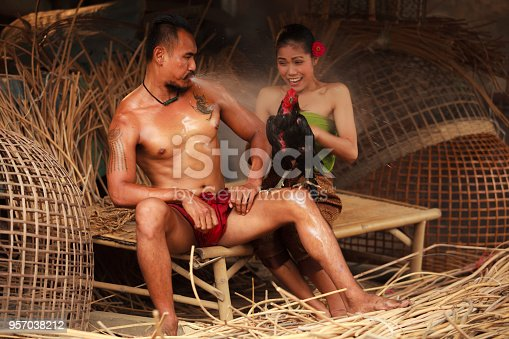 Traditional Asian Thai rural daily life, an asian man surprises nearby woman by blowing water to a fighting cock.