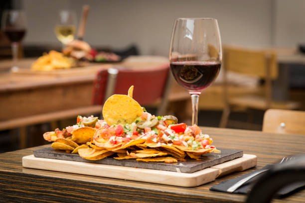 Traditional atmosphere with plate of nachos and glass of red wine stock photo
