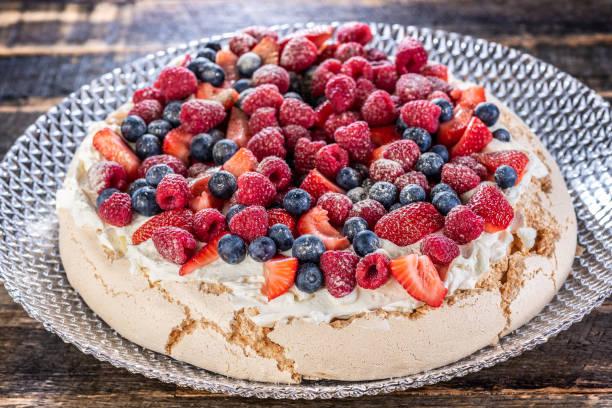A traditional Australian desert, Pavlova featuring meringue whipped cream, strawberries, blueberries, raspberries stock photo
