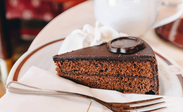 Traditional Austrian Sacher torte chocolate cake sliced on white plate stock photo