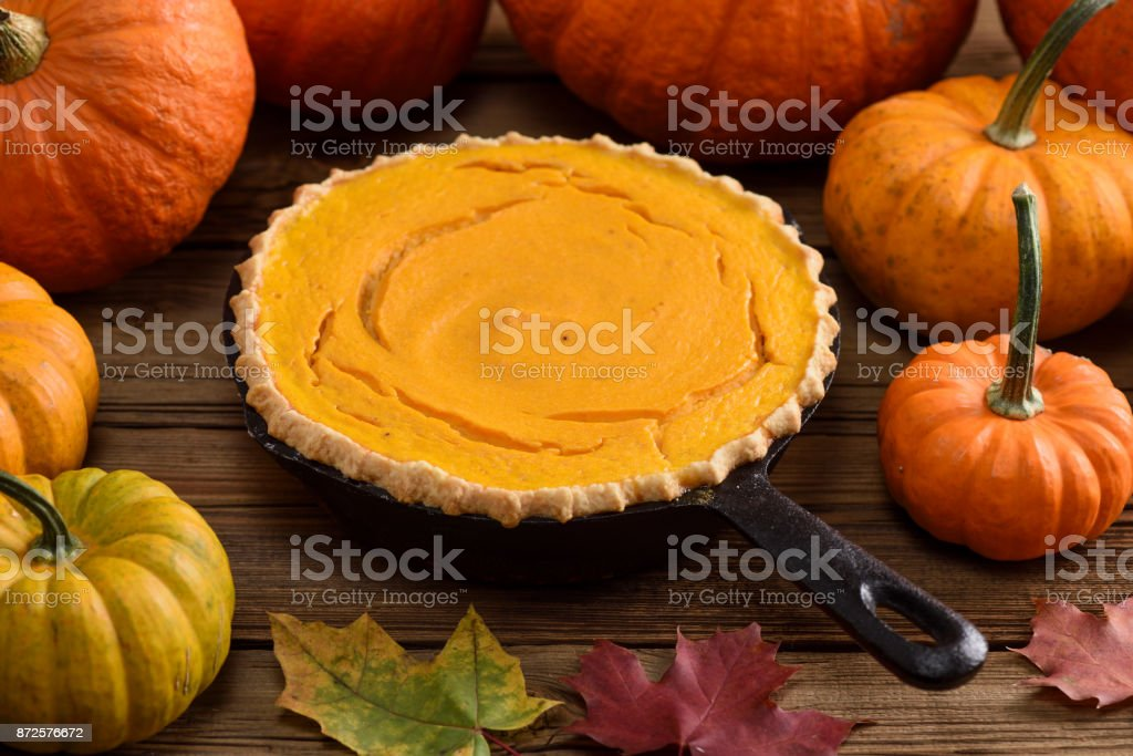 Traditional autumn dessert. Homemade pumpkin pie in cast iron pan decorated with raw pumpkins and marple leaves on wooden background stock photo