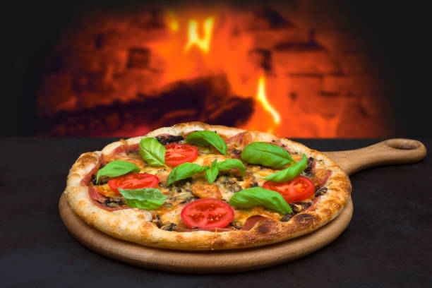 Traditional baked pizza on background of blurred brick oven fire stock photo
