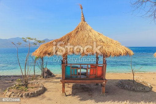 Traditional Bali gazebo,with two colorful pillow on the seater. The beach hut is on the seaside, with overlook of the blue ocean and sky.