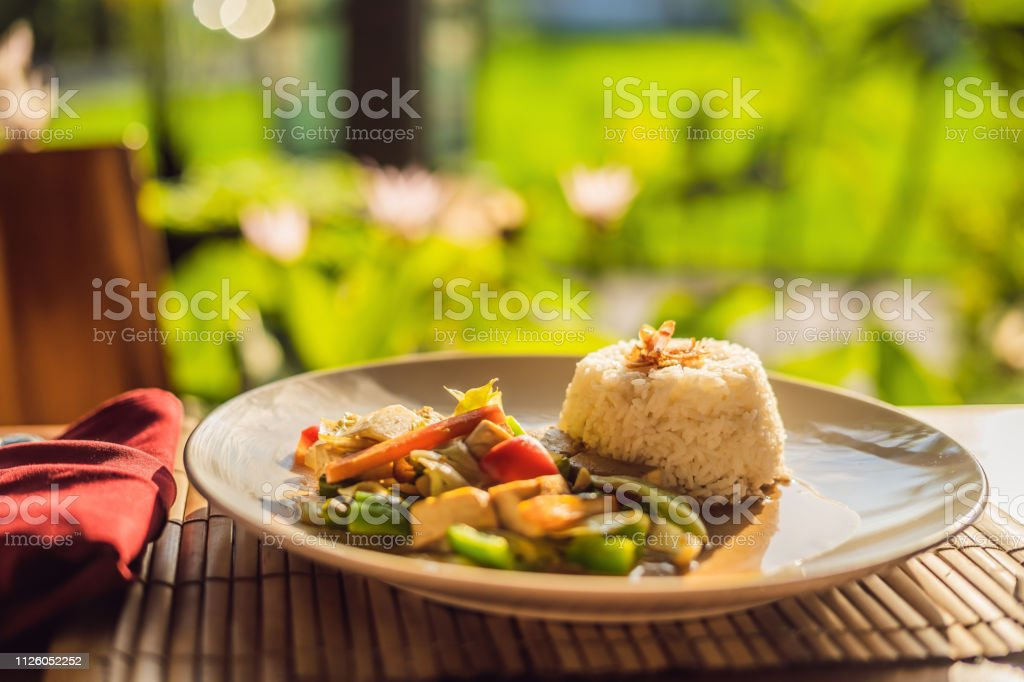 Traditional Balinese cuisine. Vegetable and tofu stir-fry with rice stock photo