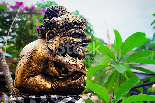 Traditional Balinese Bedogol Dwarapala decorated for festival by ceremonial offering. Protective guardian in front of doors, gates of hindu temples or houses. Bali travel, art, culture background.
