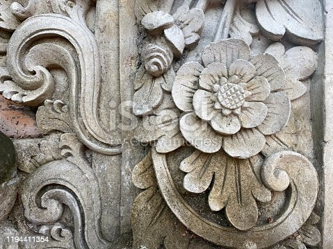 Horizontal closeup photo of a part of an old, hand-carved stone panel with floral and wave designs on a temple gateway in Ubud Bali Indonesia