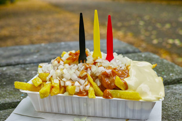 Traditional Belgian fast food, fried potatoes chips with mayonnaise, sate souse and onion served outside Traditional Belgian fast food, fried potatoes chips with mayonnaise, sate souse and onion served outside belgium stock pictures, royalty-free photos & images