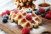 Traditional belgian waffles with fresh blueberries, sugar and raspberries.
