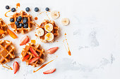 Traditional belgian waffles with fresh fruit and caramel. Flat lay