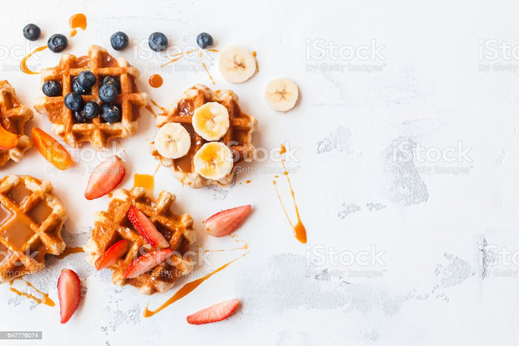 Traditional belgian waffles with fresh fruit and caramel. Flat lay stock photo