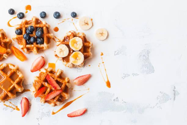 traditionelle belgische waffeln mit frischen früchten und karamell. flach zu legen - vanille waffeln stock-fotos und bilder