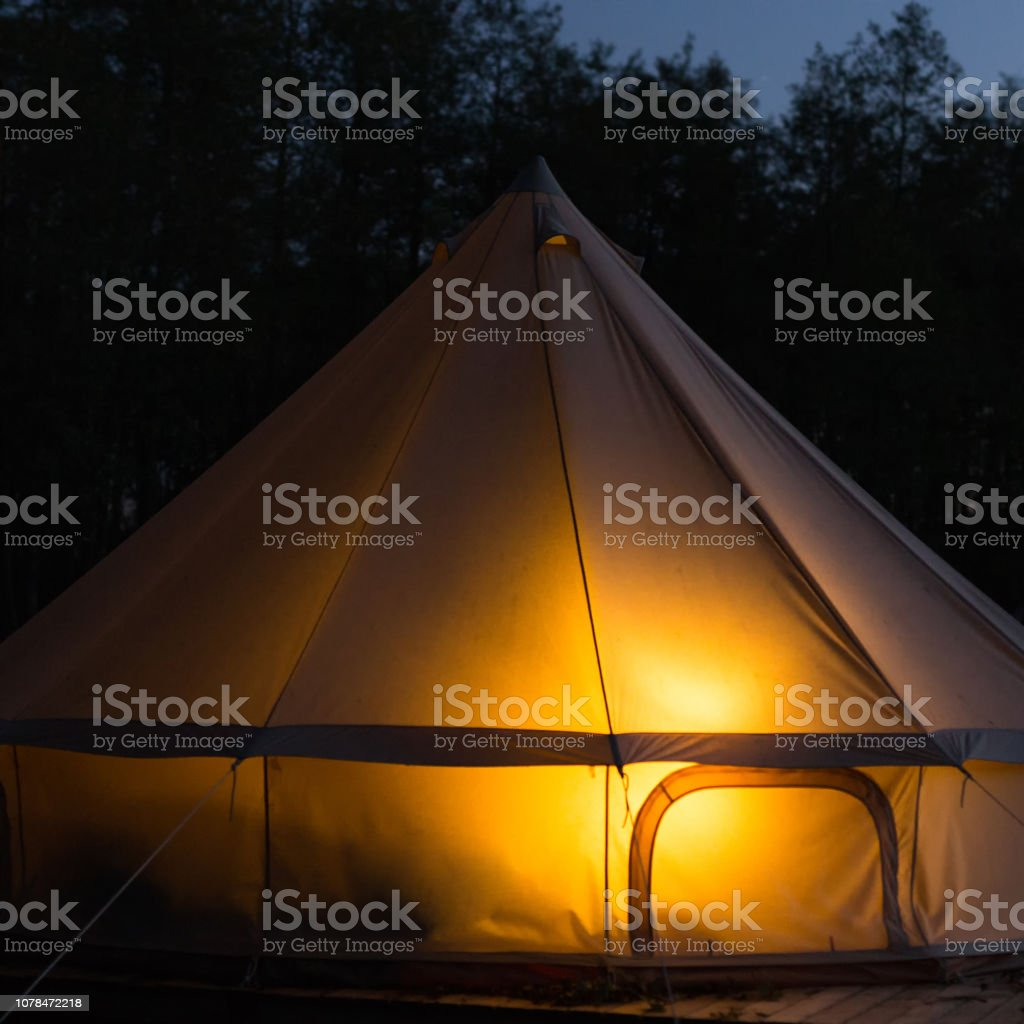 Traditional bell tent glows at night stock photo