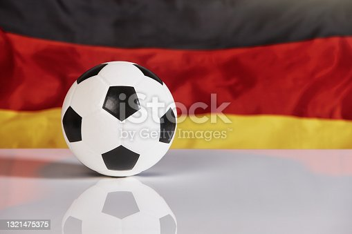 istock Traditional black and white soccer ball with the flag of Germany, representing support for the national team 1321475375