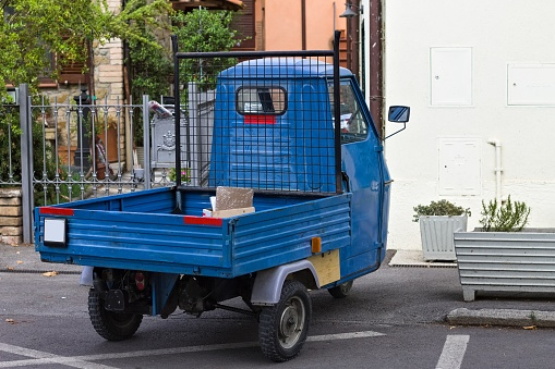 A traditional blue three-wheeled vehicle parked on the road (Tuscany, Italy, Europe)