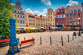 istock Traditional blue water pump with gryphon head crest from Szczecin city emblem and old town square in background 1285622224