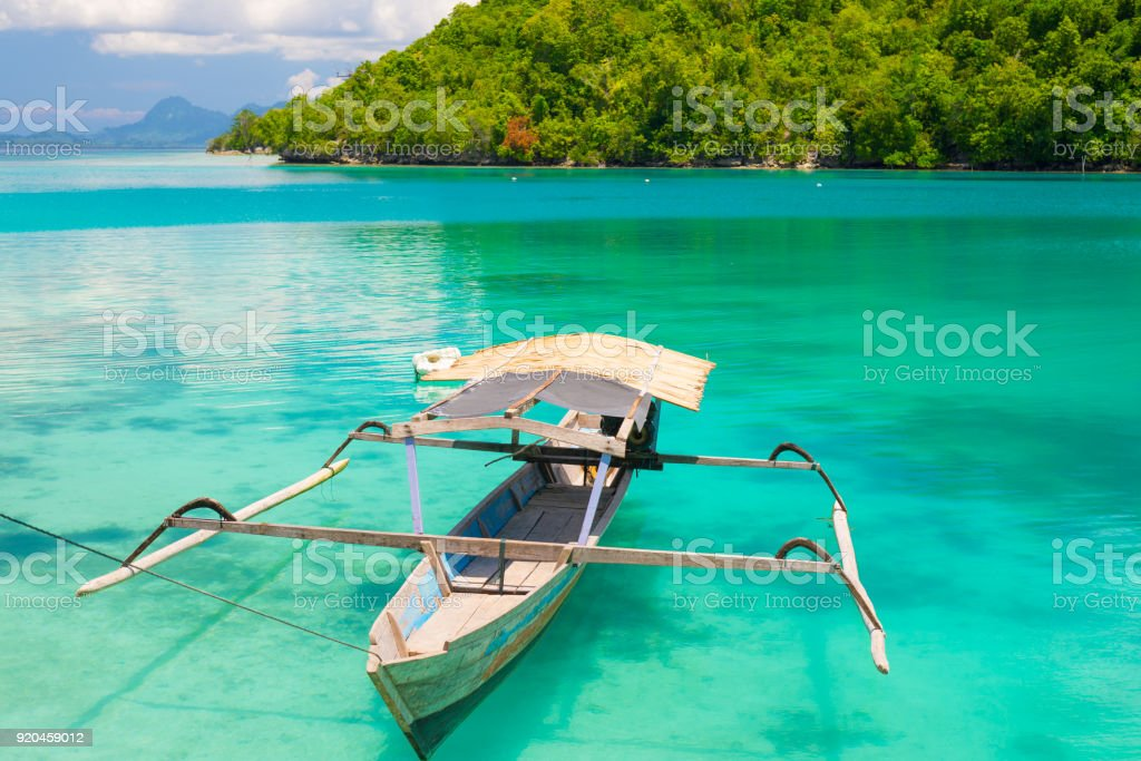 Traditional boat floating on the transparent blue toned lagoon of the remote Togean (or Togian) Islands, Central Sulawesi, Indonesia, upgrowing travel destination for young hipsters. stock photo