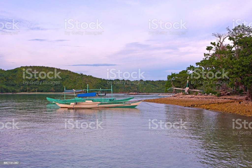 Traditional boats moored in shallow waters of the sea lagoon in early morning. stock photo
