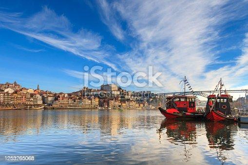 Traditional boats of the river Douro in Porto, Portugal. Oporto is an amazing tourist attraction and vacation destination in europe. Majestic travel spot. Beautiful bridge crossing Douro River.