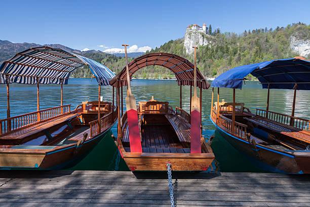 Traditionelle Boote auf Bleder See mit Bled Castle im Hintergrund – Foto