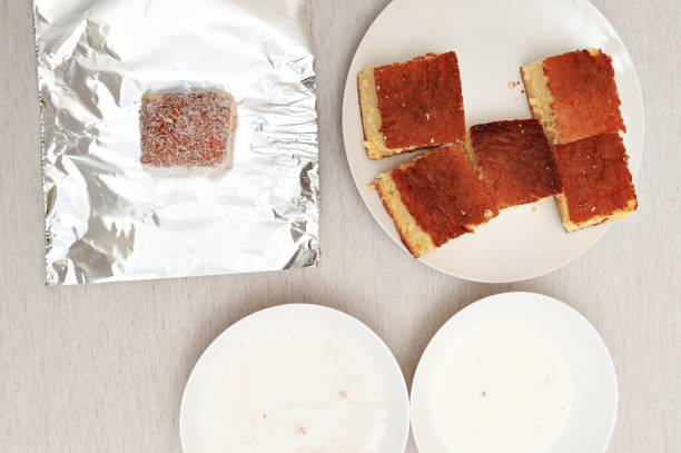 Traditional Brazilian dessert known as BOLO GELADO in Portuguese - Making step by step: Pieces of cake, aluminum foil, plates with milk and grated coconut. Top view Traditional Brazilian dessert known as BOLO GELADO in Portuguese - Making step by step: Pieces of cake, aluminum foil, plates with milk and grated coconut. Top view. gelado stock pictures, royalty-free photos & images