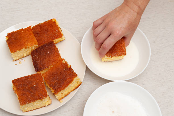 Traditional Brazilian dessert known as BOLO GELADO in Portuguese - Making step by step: Hand putting piece of cake in milk. Top view Traditional Brazilian dessert known as BOLO GELADO in Portuguese - Making step by step: Hand putting piece of cake in milk. Top view gelado stock pictures, royalty-free photos & images