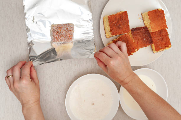Traditional Brazilian dessert known as BOLO GELADO in Portuguese - Making step by step: Hand wrapping a piece of cake in aluminum foil. Top view Traditional Brazilian dessert known as BOLO GELADO in Portuguese - Making step by step: Hand wrapping a piece of cake in aluminum foil. Top view. gelado stock pictures, royalty-free photos & images