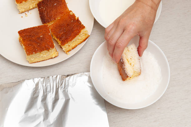 Traditional Brazilian dessert known as BOLO GELADO in Portuguese - Making step by step: Hand putting piece of cake in grated coconut. Top view Traditional Brazilian dessert known as BOLO GELADO in Portuguese - Making step by step: Hand putting piece of cake in grated coconut. Top view. gelado stock pictures, royalty-free photos & images