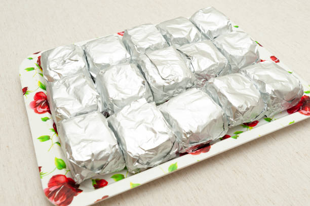"""Traditional Brazilian dessert (known as """"Bolo Gelado"""") - Making step by step: cakes wrapped in aluminum foil placed on tray. Perpendicular view. Isolated on white background. Horizontal shot Traditional Brazilian dessert (known as """"Bolo Gelado"""") - Making step by step: cakes wrapped in aluminum foil placed on tray. Perpendicular view. Isolated on white background. Horizontal shot. gelado stock pictures, royalty-free photos & images"""