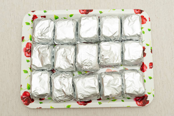 Traditional Brazilian dessert (known as Bolo Gelado) - Making step by step: cakes wrapped in aluminum foil placed on tray. Top view. Isolated on white background. Horizontal shot Traditional Brazilian dessert (known as Bolo Gelado) - Making step by step: cakes wrapped in aluminum foil placed on tray. Top view. Isolated on white background. Horizontal shot. gelado stock pictures, royalty-free photos & images