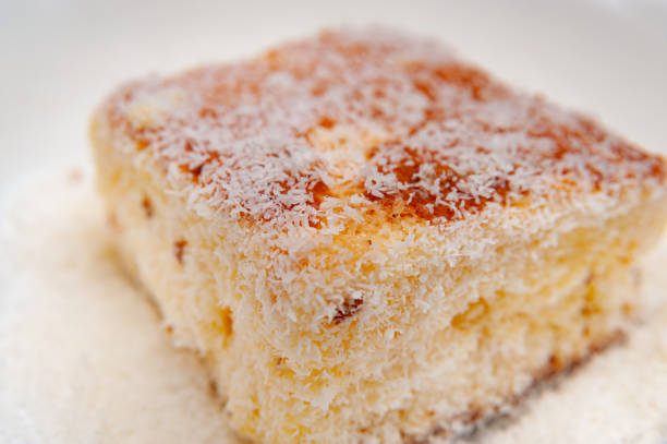 Traditional Brazilian dessert (known as Bolo Gelado) - Making step by step: Close-up of cake piece with grated coconut. Selective focus Traditional Brazilian dessert (known as Bolo Gelado) - Making step by step: Close-up of cake piece with grated coconut. Selective focus. gelado stock pictures, royalty-free photos & images