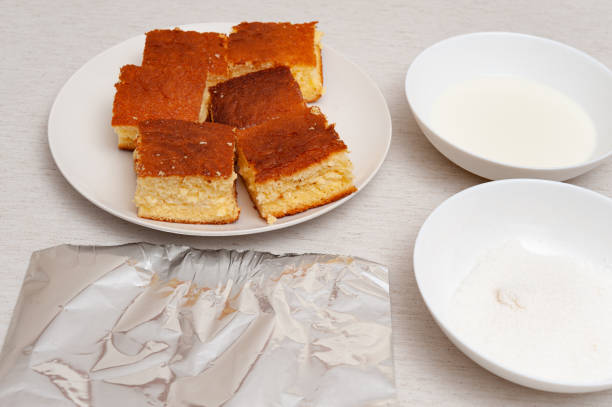 """Traditional Brazilian dessert (known as """"Bolo Gelado"""") - Making step by step: Sliced cake, bowl with milk, grated coconut and aluminum foil. Traditional Brazilian dessert (known as """"Bolo Gelado"""") - Making step by step: Sliced cake, bowl with milk, grated coconut and aluminum foil. Horizontal shot. gelado stock pictures, royalty-free photos & images"""
