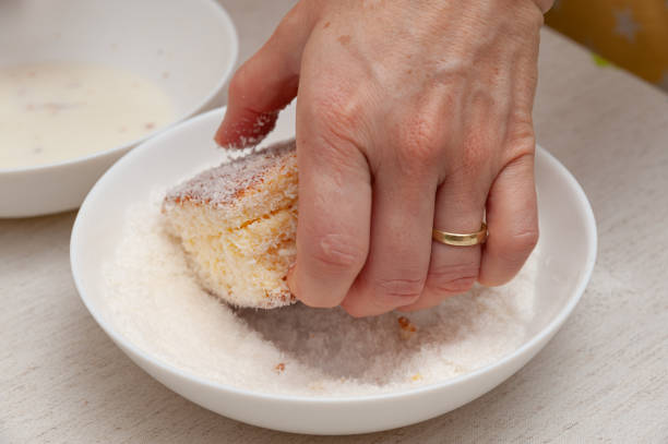 Traditional Brazilian dessert (known as Bolo Gelado) - Making step by step: Woman hand putting cake piece in grated coconut. Close-up Traditional Brazilian dessert (known as Bolo Gelado) - Making step by step: Woman hand putting cake piece in grated coconut. Close-up. gelado stock pictures, royalty-free photos & images