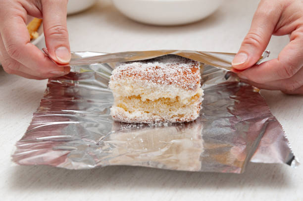 Traditional Brazilian dessert (known as Bolo Gelado) - Making step by step: Woman hand wrapping sliced cake sprinkled with granulated coconut in aluminum foil. Close-up Traditional Brazilian dessert (known as Bolo Gelado) - Making step by step: Woman hand wrapping sliced cake sprinkled with granulated coconut in aluminum foil. Close-up. gelado stock pictures, royalty-free photos & images