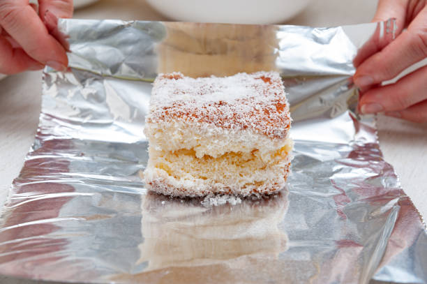 Traditional Brazilian dessert (known as Bolo Gelado) - Making step by step: Woman hand wrapping sliced cake sprinkled with granulated coconut in aluminum foil. Close-up. Horizontal shot Traditional Brazilian dessert (known as Bolo Gelado) - Making step by step: Woman hand wrapping sliced cake sprinkled with granulated coconut in aluminum foil. Close-up. Horizontal shot. gelado stock pictures, royalty-free photos & images
