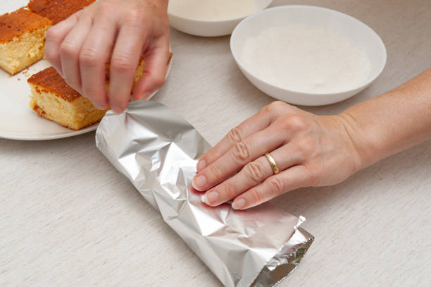 Traditional Brazilian dessert (known as Bolo Gelado) - Making step by step: Woman hand wrapping sliced cake in aluminum foil Traditional Brazilian dessert (known as Bolo Gelado) - Making step by step: Woman hand wrapping sliced cake in aluminum foil. gelado stock pictures, royalty-free photos & images