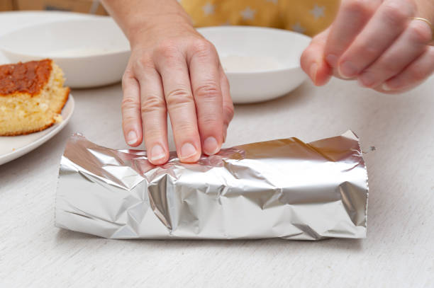 Traditional Brazilian dessert (known as Bolo Gelado) - Making step by step: Woman hand wrapping sliced cake in aluminum foil. Close-up Traditional Brazilian dessert (known as Bolo Gelado) - Making step by step: Woman hand wrapping sliced cake in aluminum foil. Close-up. gelado stock pictures, royalty-free photos & images