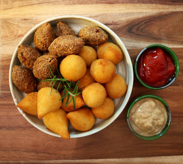Traditional Brazilian snacks coxinha and quibe on wooden background. Top view. stock photo