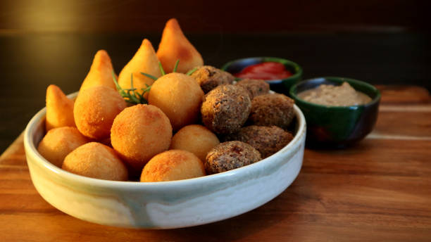 Traditional Brazilian snacks coxinha and quibe on wooden dark background. Selective focus. stock photo