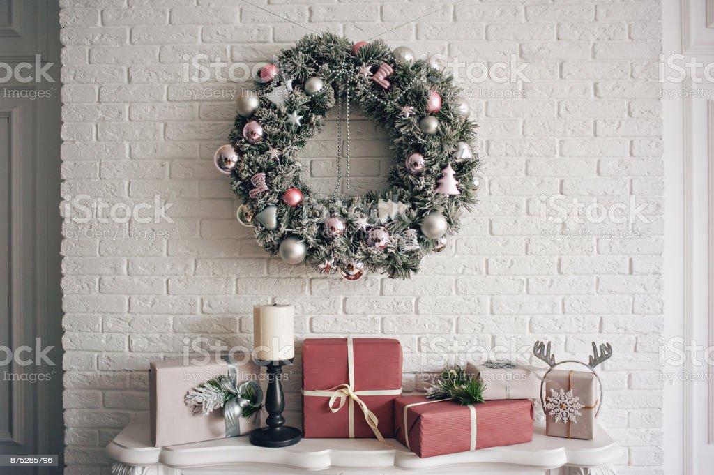 Une traditionnelle lumineuse guirlande de Noël suspendu au-dessus de la cheminée, sur une brique blanche mur et cadeaux emballés est empilés sur une cheminée avec des bougies. photo libre de droits
