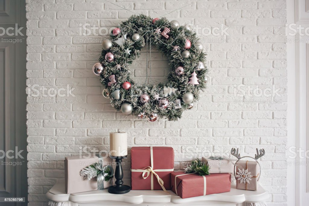 En traditionell ljusa jul krans hängande över eldstaden, på en vit tegel är vägg och paketerade gåvor staplade på en spis med ljus. bildbanksfoto