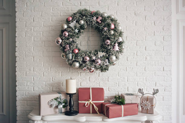 A traditional bright Christmas wreath hanging over the fireplace, on a white brick wall, and packaged gifts are stacked on a fireplace with candles. stock photo