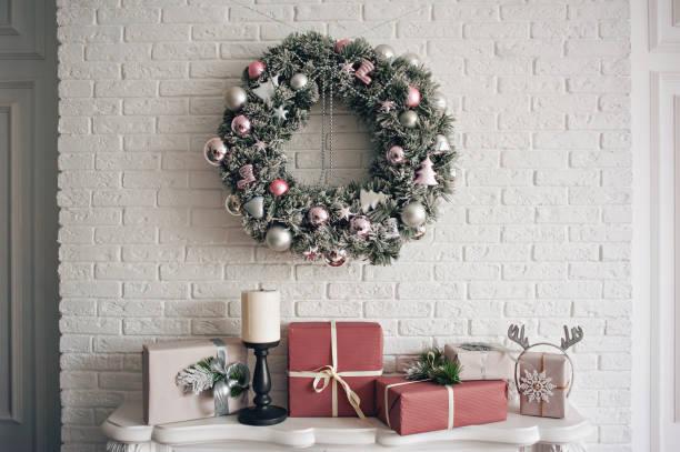 eine traditionelle hell weihnachtskranz über dem kamin hängen, sind auf einen weißen stein wand und verpackte geschenke auf einen kamin mit kerzen gestapelt. - kamin weiß stock-fotos und bilder